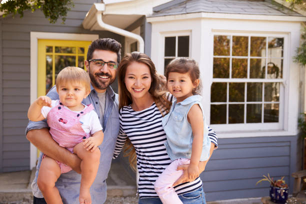 portrait of excited family standing outside new home - mixed race person stock pictures, royalty-free photos & images