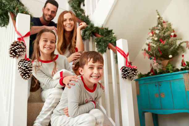 portrait of excited family wearing pajamas sitting on stairs on christmas morning - family christmas imagens e fotografias de stock