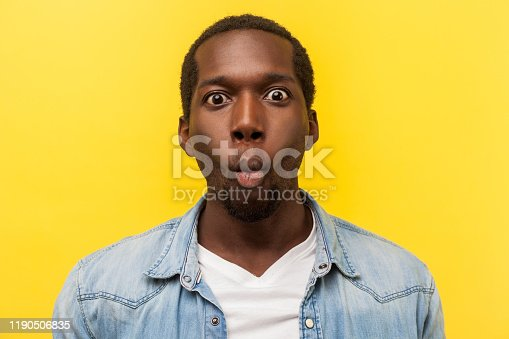 Portrait of excited funny man in denim shirt making fish face with lips and big amazed eyes, looking surprised and silly at camera, wondered expression. studio shot isolated on yellow background