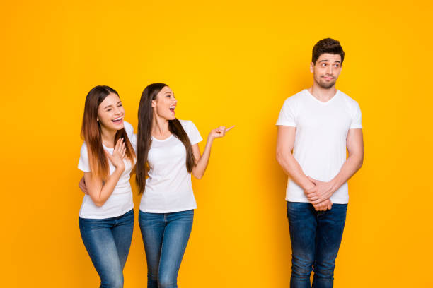 portrait of excited girls mocking at guy standing shy wearing white t-shirt denim jeans isolated over yellow background - disdainful stock pictures, royalty-free photos & images