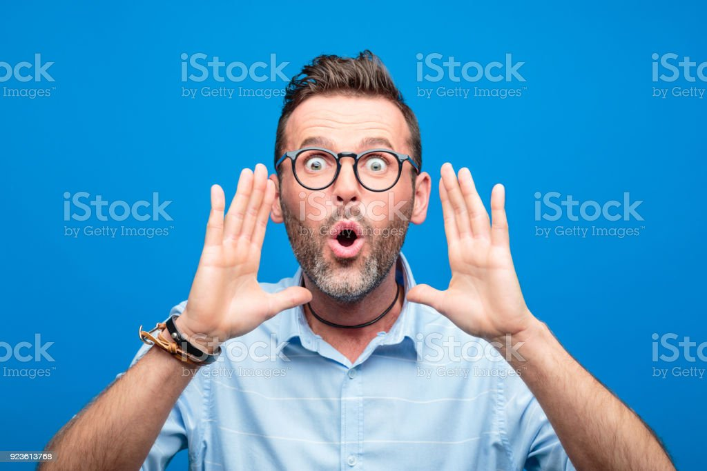 Portrait of excited handsome man screaming into camera Summer portrait of handsome man wearing blue shirt and glasses, screaming into camera. Studio shot, blue background. 30-39 Years Stock Photo