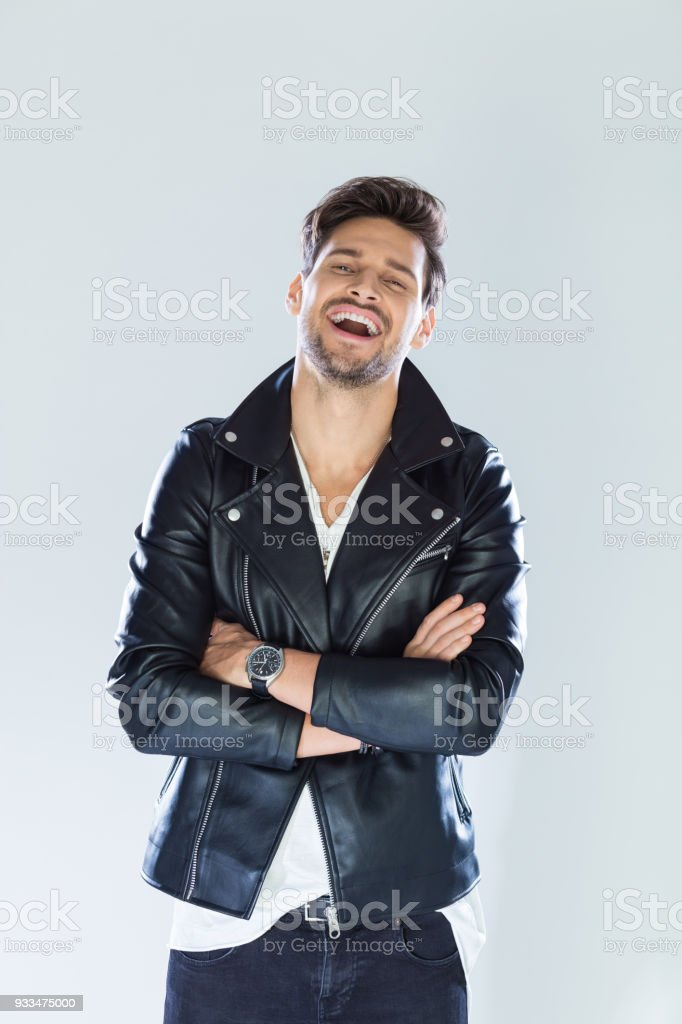 Portrait of excited handsome man wearing leather jacket Fashion portrait of handsome man wearing black leather jacket, laughing at camera. Studio shot, grey background. 25-29 Years Stock Photo