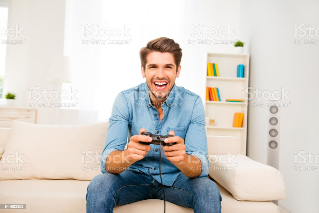 Portrait of excited happy cheerful man playing video game stock photo