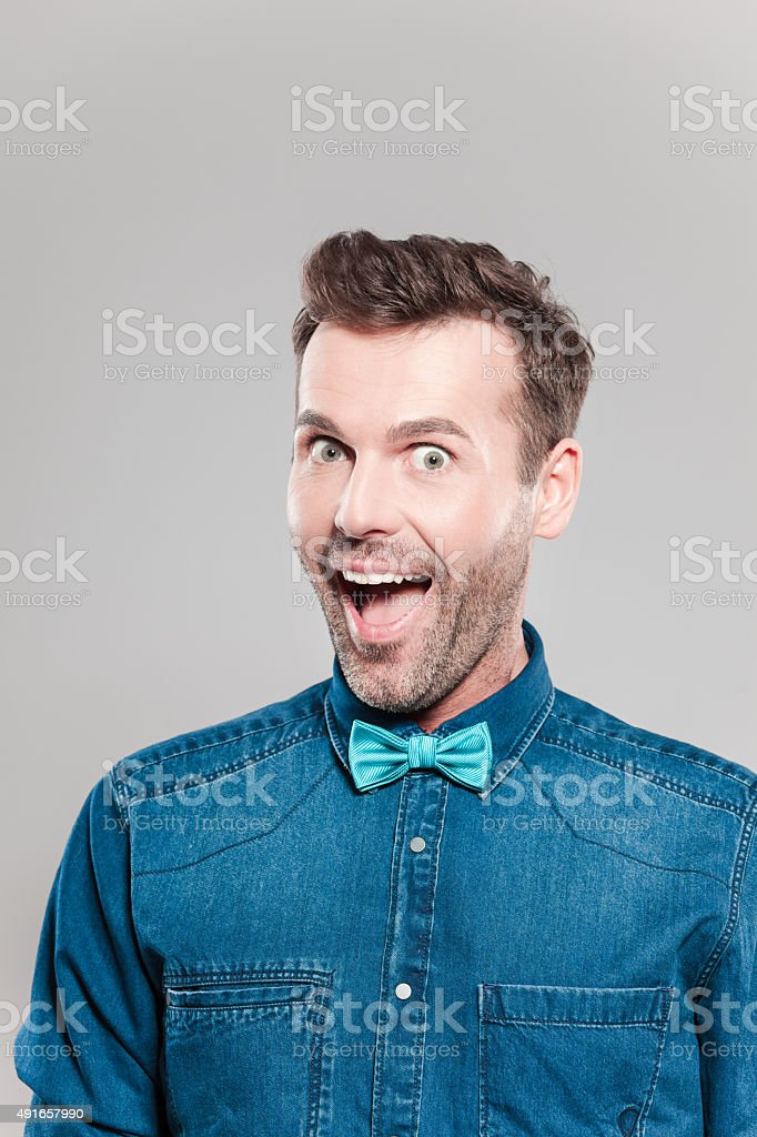 Portrait of excited man wearing jeans shirt and bow tie stock photo