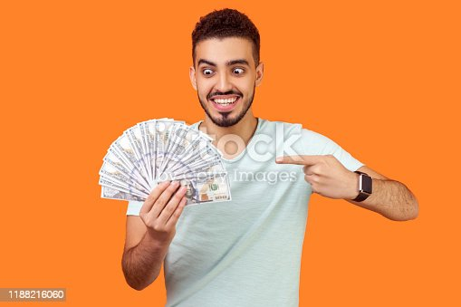 istock Portrait of excited rich brunette man pointing and looking at dollar banknotes with crazy smile. indoor studio shot isolated on orange background 1188216060