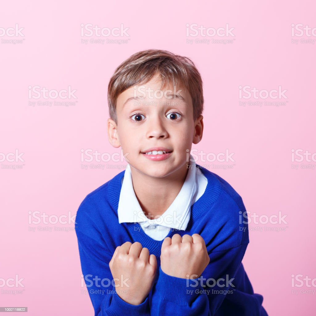 Portrait of excited schoolboy cheering against pink background Excited schoolboy wearing school uniforms clenching his fists. Studio shot, pink background. 8-9 Years Stock Photo