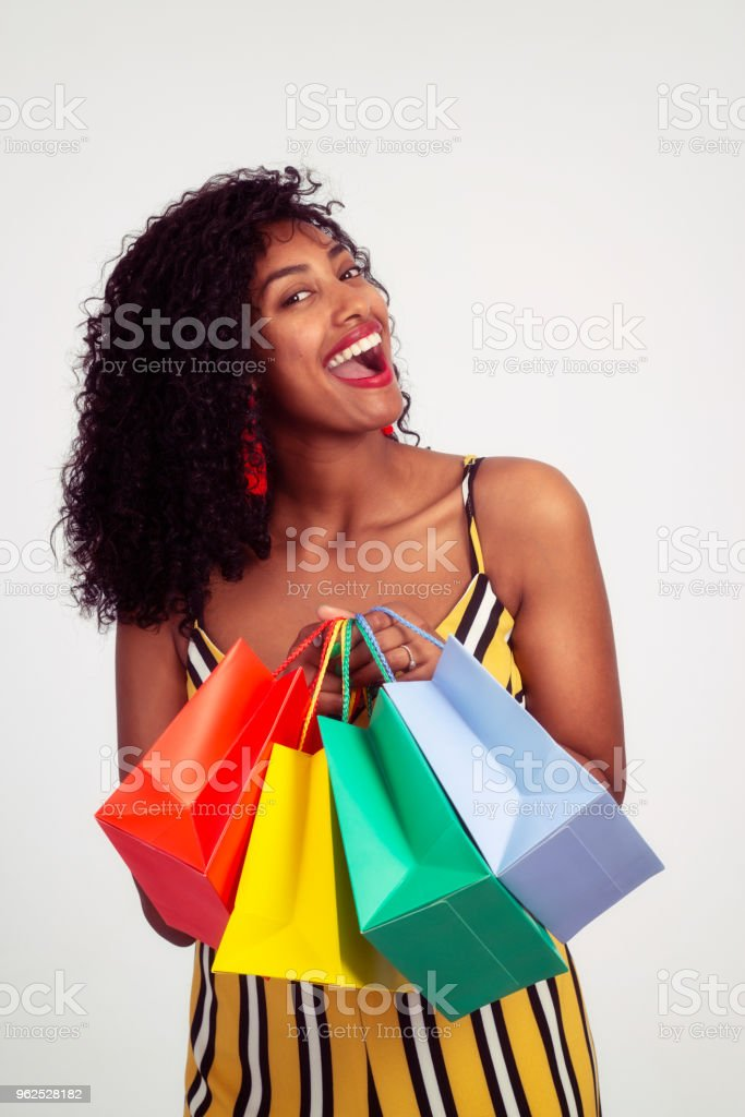 eefcd1bbdfb5c Portrait of excited shopper woman holding color shopping bags in front of  the body. royalty