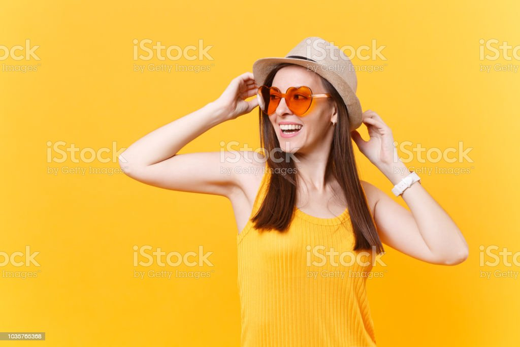Portrait of excited smiling young woman in straw summer hat, orange...