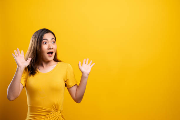 Portrait of excited woman isolated over yellow background stock photo