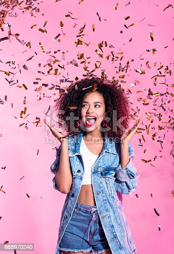 istock Portrait of excited young afro woman among confetti 688970240