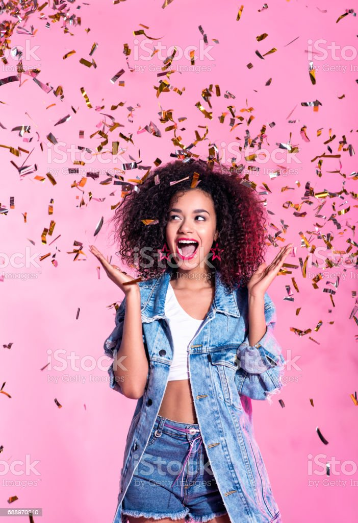 Portrait of excited young afro woman among confetti stock photo