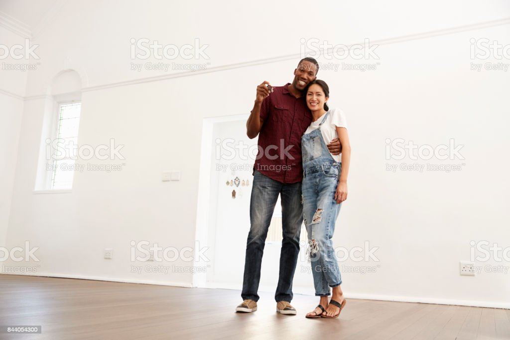 Portrait Of Excited Young Couple Moving Into New Home Together stock photo
