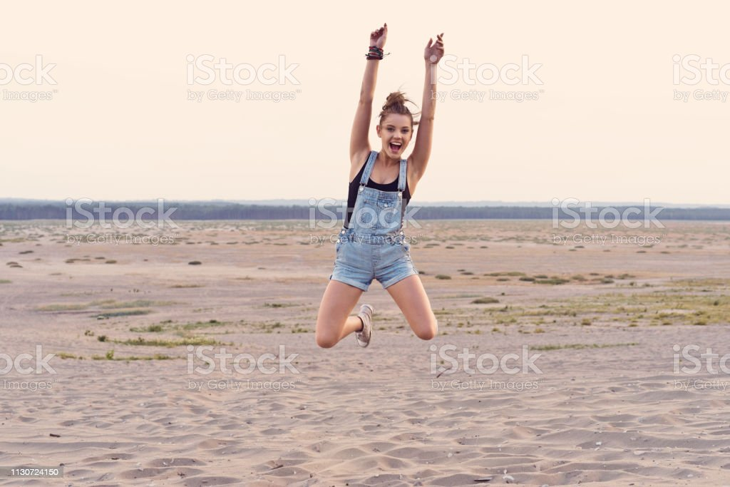 Portrait of excited young woman jumping at desert Portrait of excited young woman jumping at desert. Beautiful woman is screaming while raising arms in mid-air. She is wearing bibs overall during vacation. 25-29 Years Stock Photo
