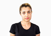 Front view portrait of frustrated young woman against white background. Worried teenage girl looking at camera with negative,helpless facial expression. Hopeless girl wearing a black t-shirt. Front view, studio shot, developed from Raw format, horizontal composition. Image taken isolated on white. Young woman has got short, brown hair and ponytail hairstyle.