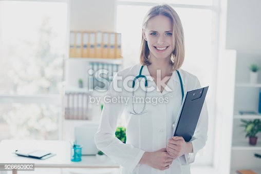 istock Portrait of experienced qualified confident smiling doctor wearing formal coat, she is holding clipboard, standing against her workplace 926660902