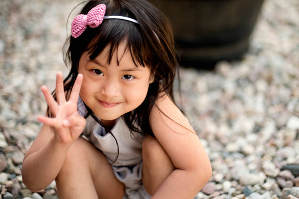 Portrait of expressive four year's old asian girl outdoors. stock photo