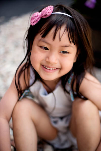 Portrait of expressive little asian girl outdoors. stock photo
