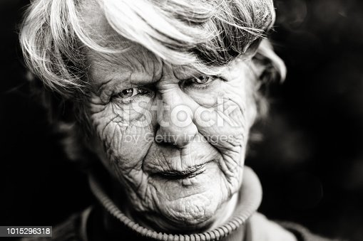 A very old woman frowns unhappily in this black and white portrait.