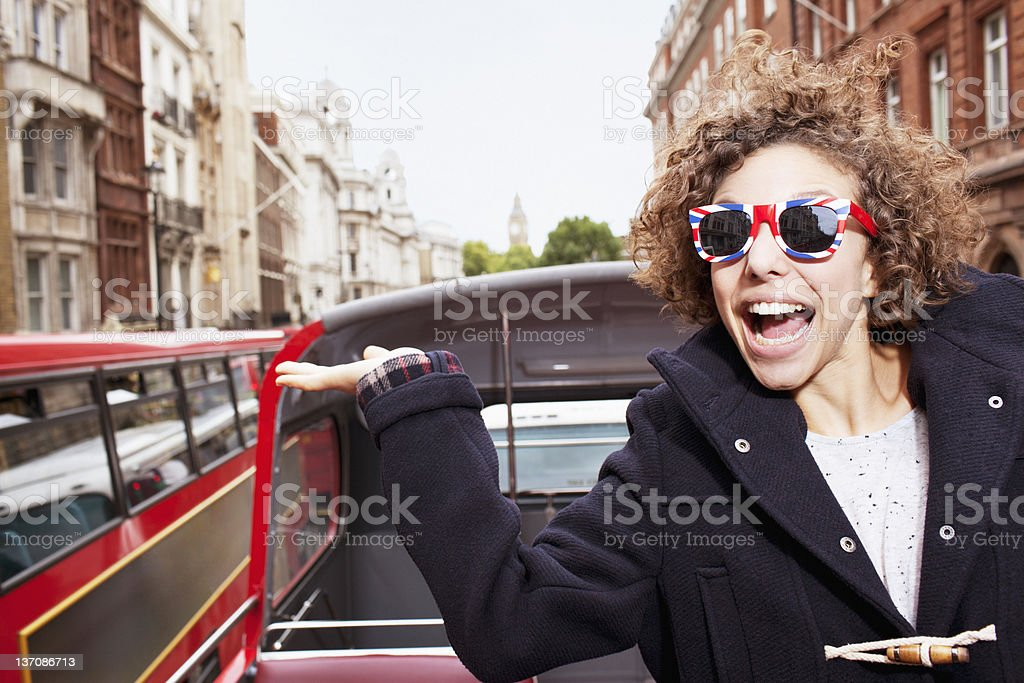 Portrait of exuberant woman wearing British flag sunglasses and riding double decker bus in London stock photo