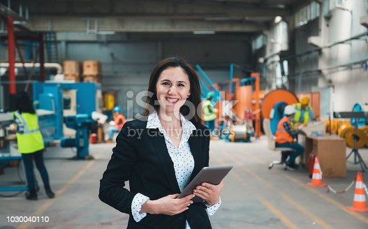 915900234istockphoto Portrait of factory manager woman using tablet 1030040110