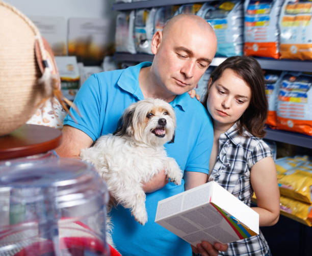 portrait of  family couple with dog  choosing dry food in pet store - pet shop and dogs not cats stock pictures, royalty-free photos & images