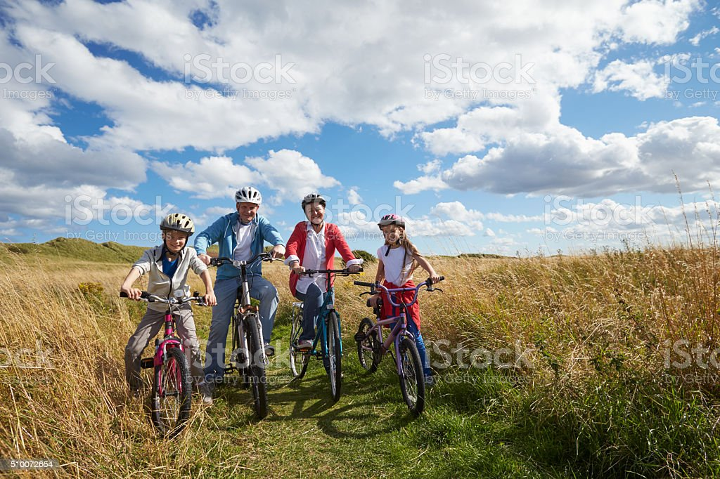 Portrait Of Family Cycling Through Countryside Together stock photo