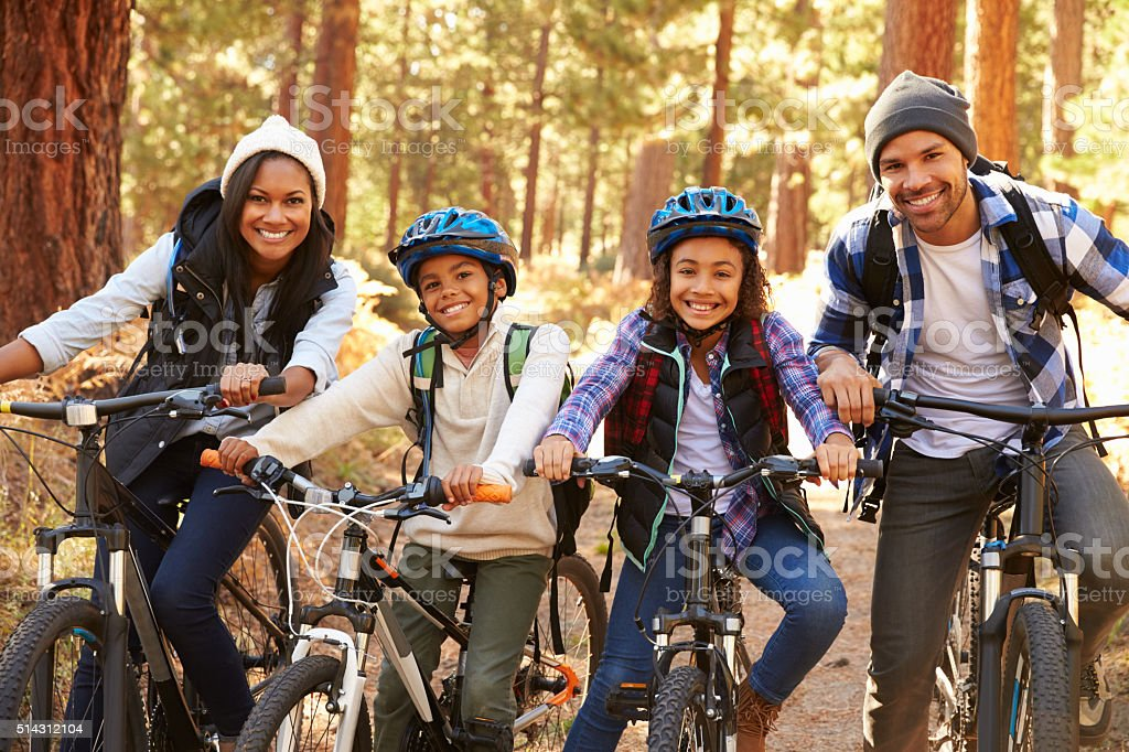 Portrait Of Family Cycling Through Fall Woodland stock photo