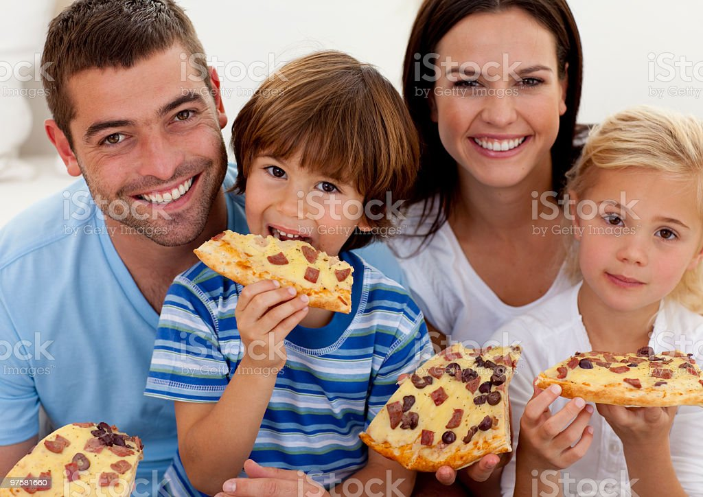 Portrait de famille manger la pizza dans le salon photo libre de droits