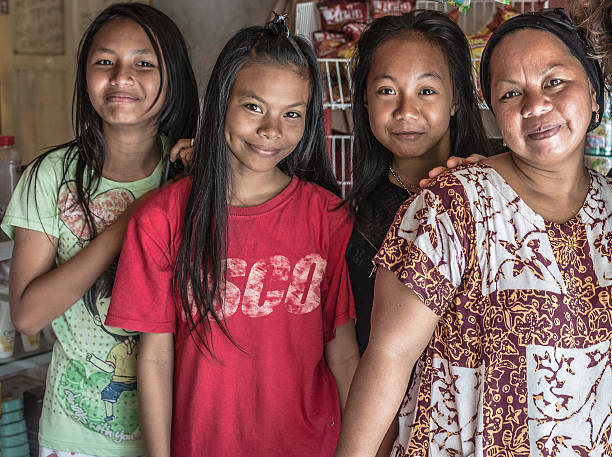 Portrait of family from Sulawesi, Indonesia Boneoge, Sulawesi, Indonesia - August 31, 2014: Portrait of local family of indonesian ethnicity, 3 young girls and 1 adult lady, smiling while looking at the camera in the village of Boneoge, Central Sulawesi, Indonesia. indonesian ethnicity stock pictures, royalty-free photos & images