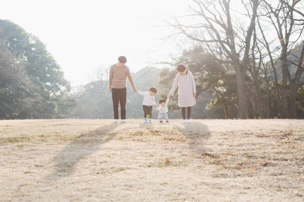一緒にお互いの手を保持している家族の肖像 - 家族 日本人 ストックフォトと画像