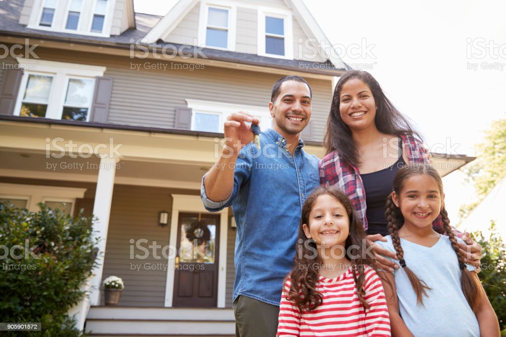 Portrait Of Family Holding Keys To New Home On Moving In Day stock photo