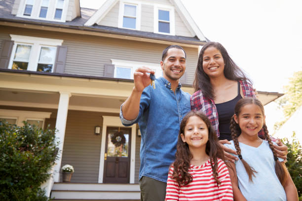 portrait of family holding keys to new home on moving in day - house hunting stock photos and pictures