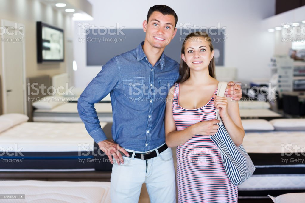 Portrait of positive young family couple in mattress store