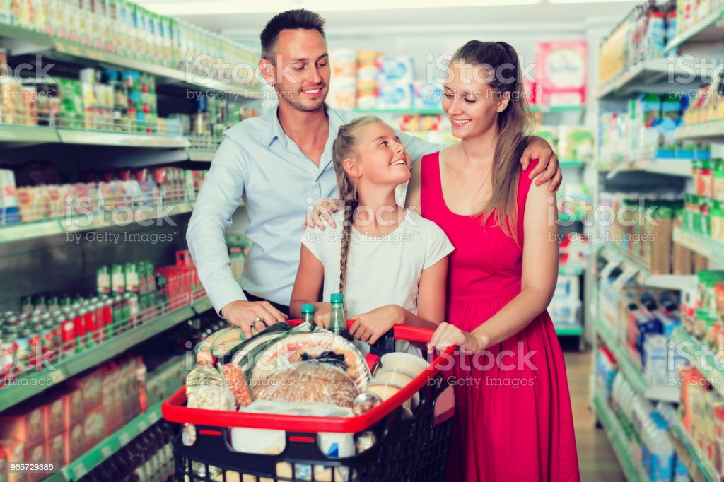 Portrait of family of three which is standing with full trolley of goods - Royalty-free 1910-1919 Stock Photo