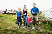 A portrait of a family of urban farmers holding their tools.