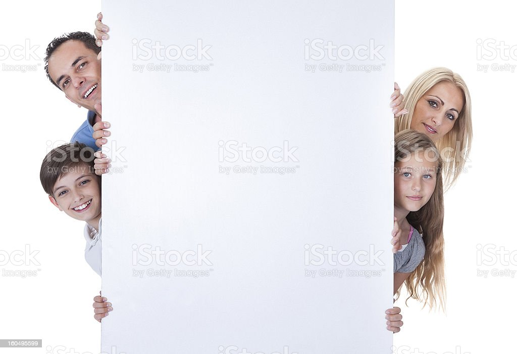 Portrait Of Family Peeping Behind Blank Board royalty-free stock photo