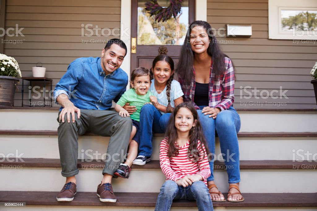 Portrait Of Family Sitting On Steps in Front Of House stock photo