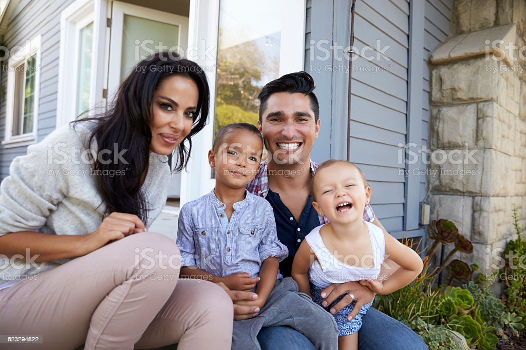 Portrait Of Family Sitting On Steps Outside Home stock photo