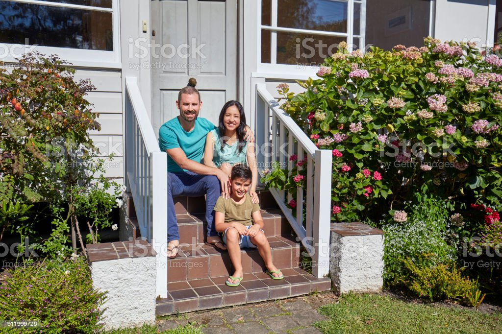 Portrait of family sitting on steps outside house stock photo