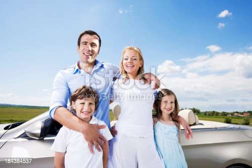 istock Portrait of family standing near Convertible car. 184384537