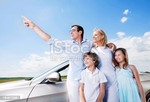 istock Portrait of family standing near Convertible car. 184879881