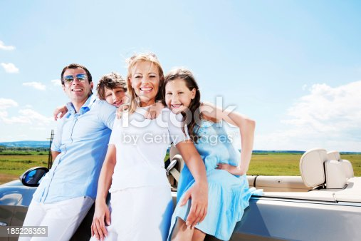 528474010istockphoto Portrait of family standing near Convertible car 185226353