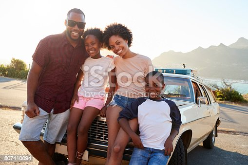 807410158 istock photo Portrait Of Family Standing Next To Classic Car 807410094