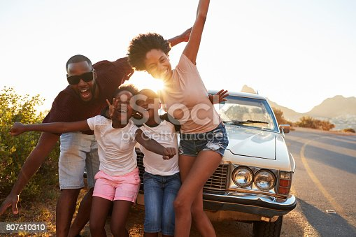 807410158 istock photo Portrait Of Family Standing Next To Classic Car 807410310