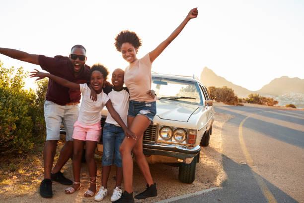 porträt der familie stehen neben oldtimer - afrika urlaub stock-fotos und bilder