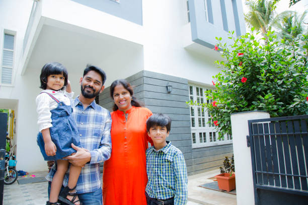 Portrait Of Family Standing Outside Home stock photo Family, Child, Father, Smiling, Mixed Race Person indian family stock pictures, royalty-free photos & images