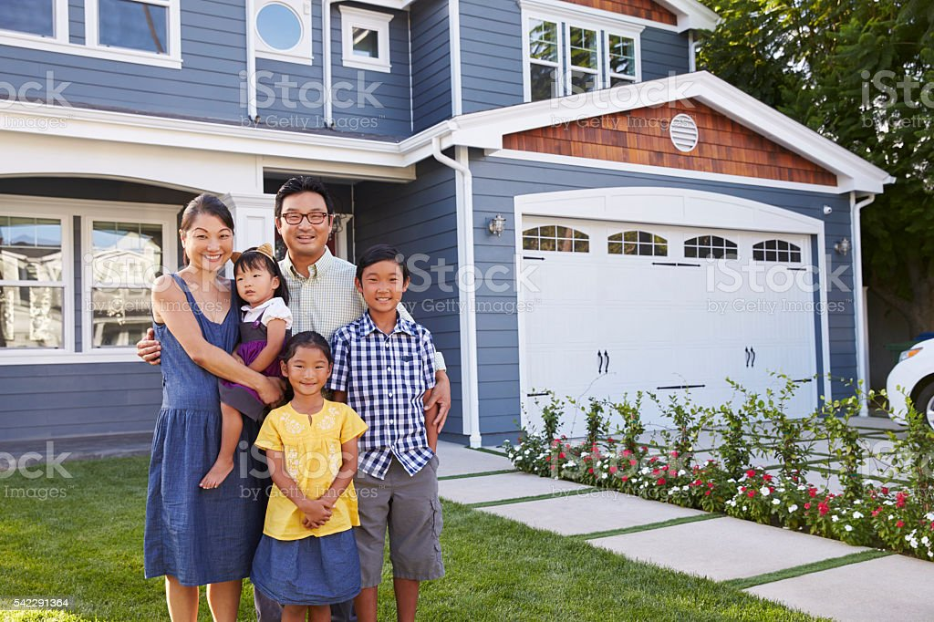 Portrait Of Family Standing Outside House stock photo