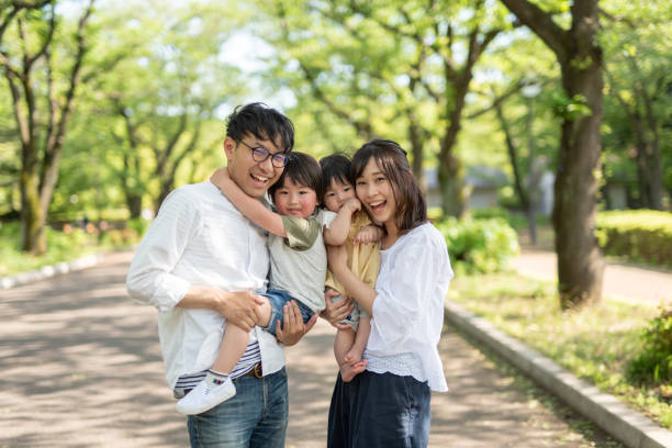 Portrait of family under trees Portrait of family in tree area japanese ethnicity stock pictures, royalty-free photos & images