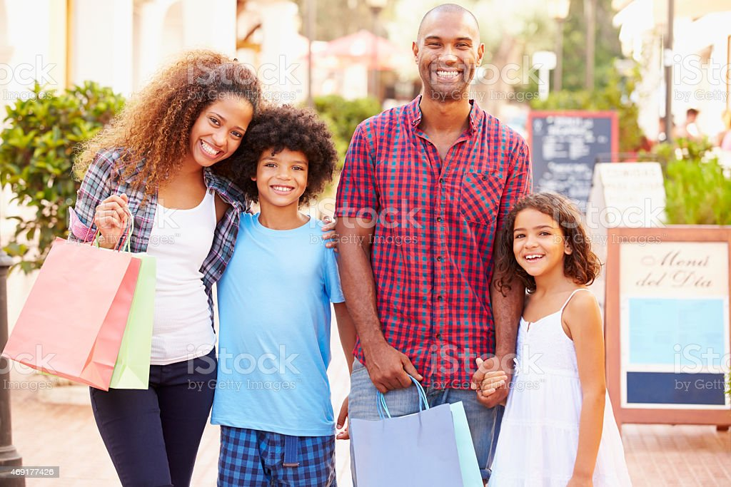 Portrait Of Family Walking Along Street With Shopping Bags stock photo