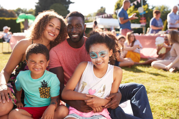 Portrait Of Family With Children Sitting On Rug At Summer Garden Fete Portrait Of Family With Children Sitting On Rug At Summer Garden Fete carnival celebration event stock pictures, royalty-free photos & images